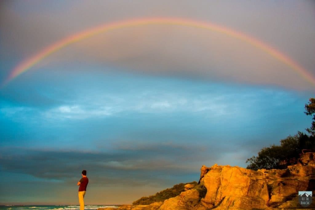 Across the Ditch To Minjerribah // Stradbroke Island (QLD), Jacquie Tapsall, rainbow, person, headland, ocean,