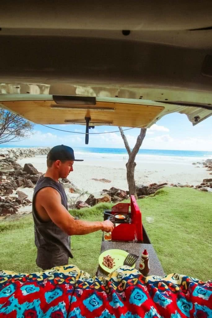 Why You Should Start Living An Adventurous Lifestyle Scout Hinchcliffe, vanlife, barbecue, breakfast, cooking, beach, ocean, view
