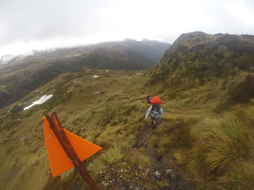 The Hardest Hike in New Zealand // Dusky Track, Tim Ashelford, photo by mitch stewart, hiker, cloudy, heath, grassland, track, snow, mountains, ski marker triangle, rain cover