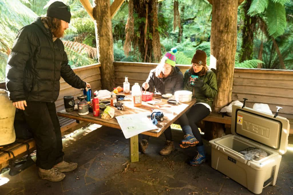 Yeti Tundra Esky Gear Review Sheltered Lunch Pat Corden, shelter, lunch, women, three people, wooden hut, table, picnic
