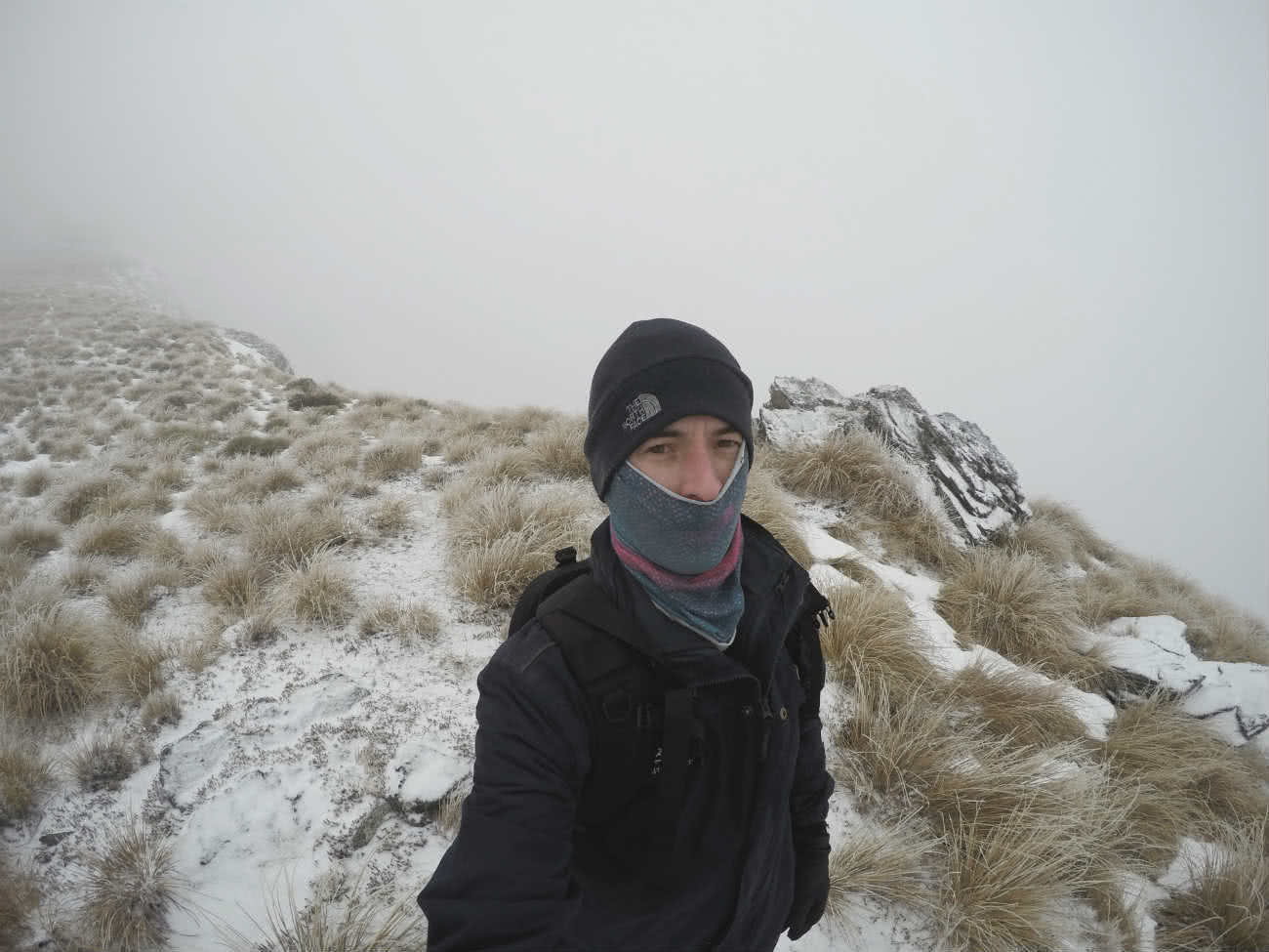 Snow trekking above Queenstown NZ Calumn Hockey, snow trekking, hiker, snow, beanie, wooly hat, mountains, fog, damn cold