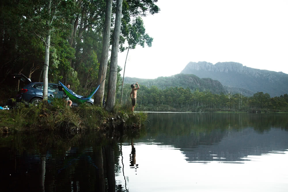 12 Things To Do On Tassie's West Coast, photo by Nick Green, Lake rosebury, man, hammock, mountains, forest
