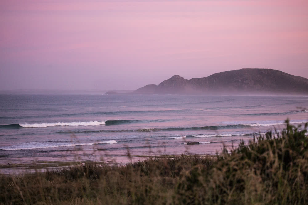 12 Things To Do On Tassie's West Coast, Green Point Beach, ocean, waves, sunset, pink sky, grass, beach