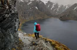 Soggy, Snowbound And Stoked // Routeburn Track (NZ), Rachel Dimond, Day 2 - The Saddle and Harris Lake 2, rain gear, backpack, rain cover, lake, snowcapped mountains