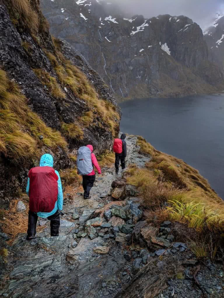 Soggy, Snowbound And Stoked // Routeburn Track (NZ), Rachel Dimond, Day 2 - The Saddle and Harris Lake, hikers, waterproofs, backpack, rain covers, lake, path, trail