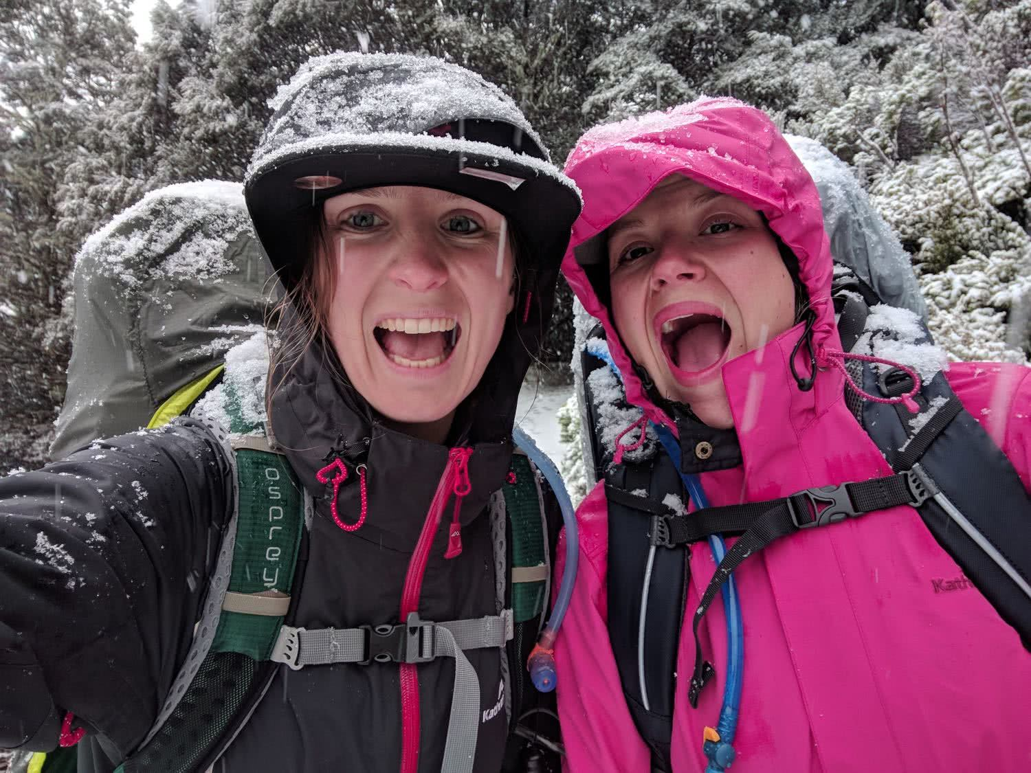 Soggy, Snowbound And Stoked // Routeburn Track (NZ), Rachel Dimond, Day 3 - Two girls in a snow storm, stoked, happy, smiles, waterproofs, backpacks, fun