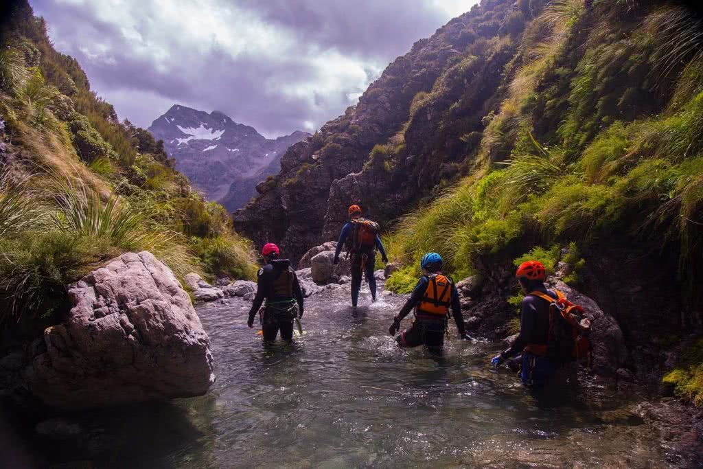 Ode To The River // Canyoning And Packrafting In New Zealand, Xavier Anderson, wading, crew, group, helmets, view, mountains