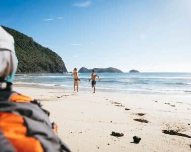 Howe To Budget // Cheap Stays On Lord Howe Island, Scout Hincliffe, photo Henry Brydon, backpackers, footprints, sand, running, beach, swimsuits, snorkels, water