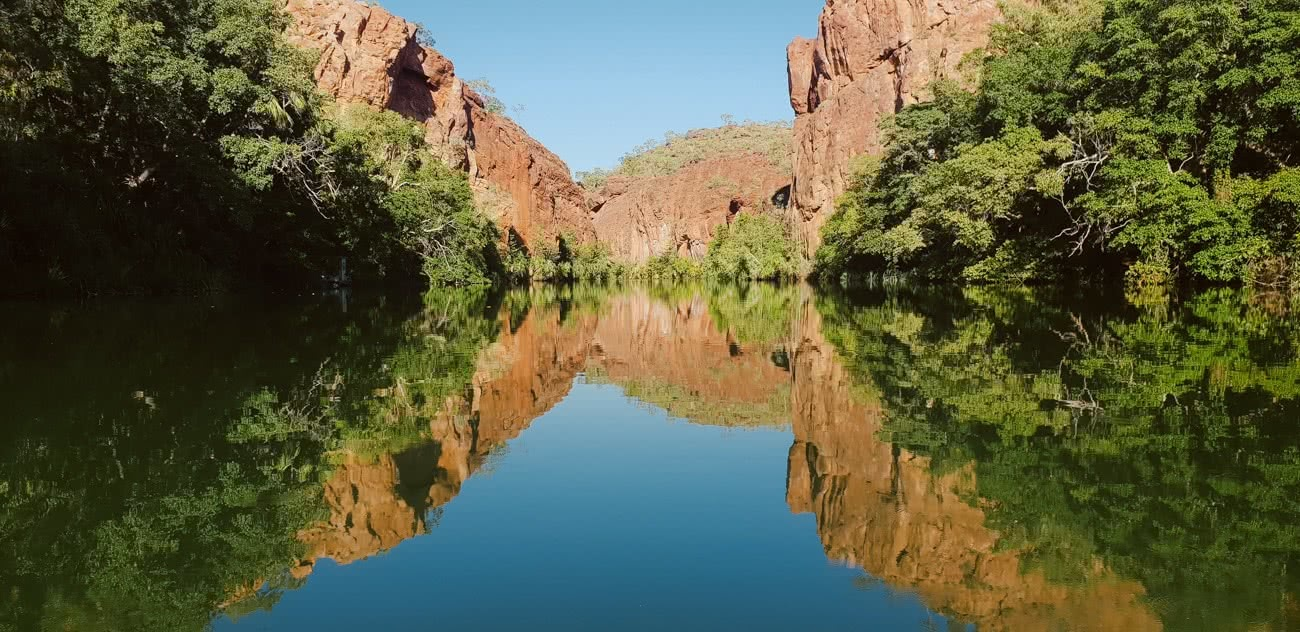 Out There In An Outback Oasis // Adels Grove (QLD), Grace and Brenton Keller, glassy, mirror, reflection, cliffs, red rock, bush, swimming hole, lawn hill creek