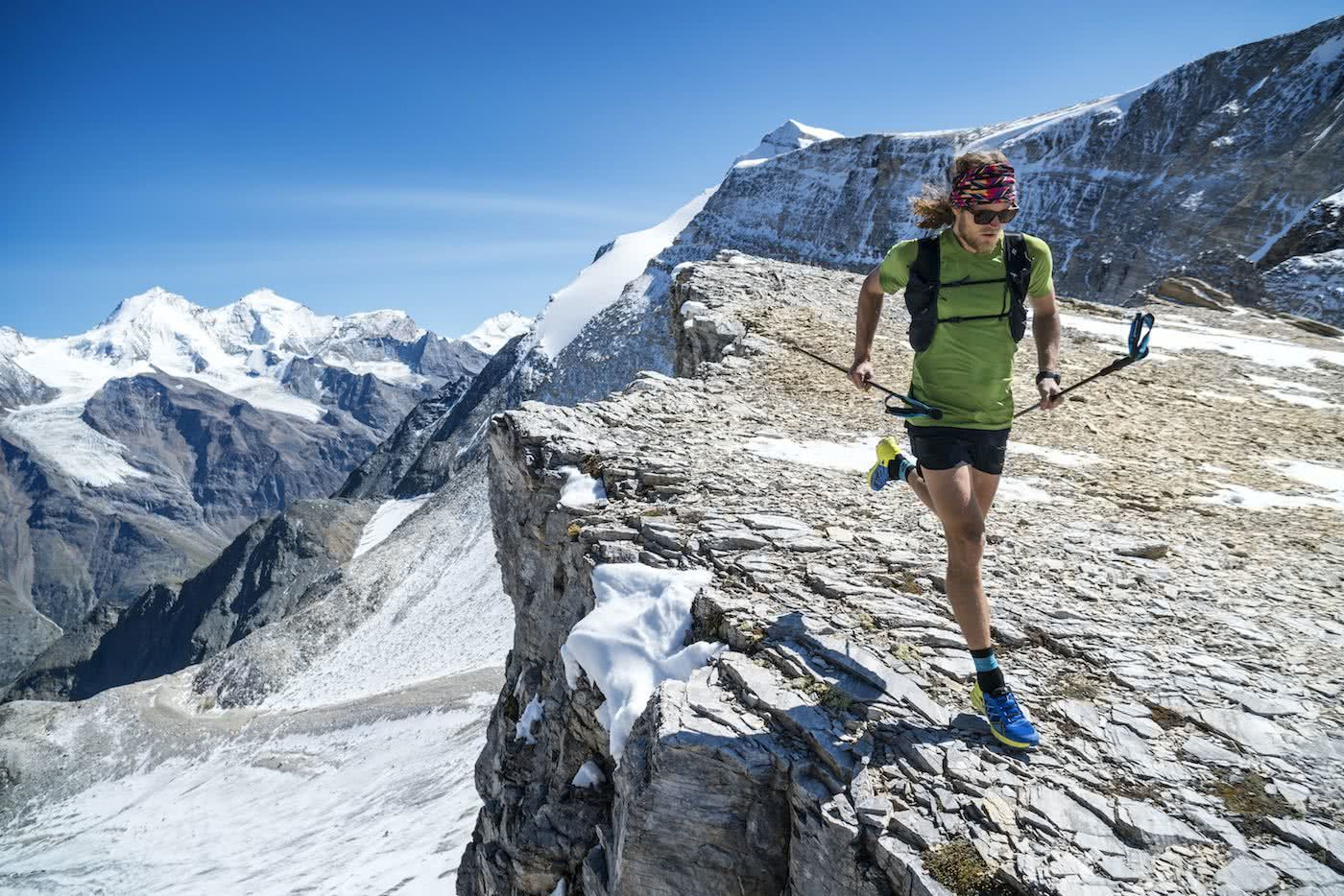 Runner Guy // An Interview With Trail Runner Joe Grant, Photo by Dan Patitucci, running poles, cliff edge, mountain, snow