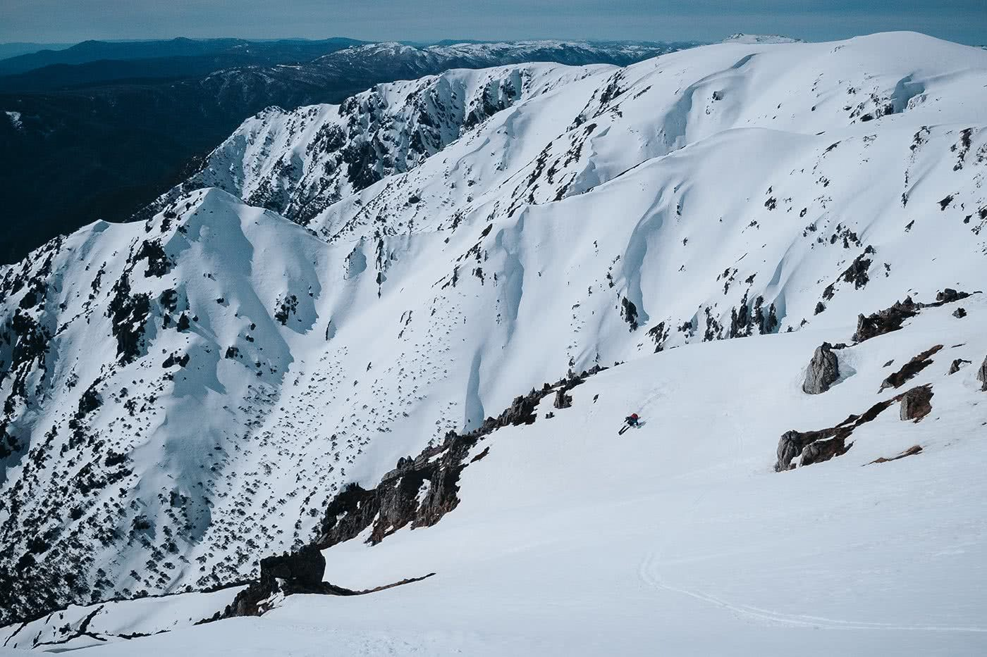 Wait, Australia Has Backcountry Skiing? Is It Any Good? Photo by Ain Raadick or Ben Savage, Arc'teryx event, snow, cliff, mountains