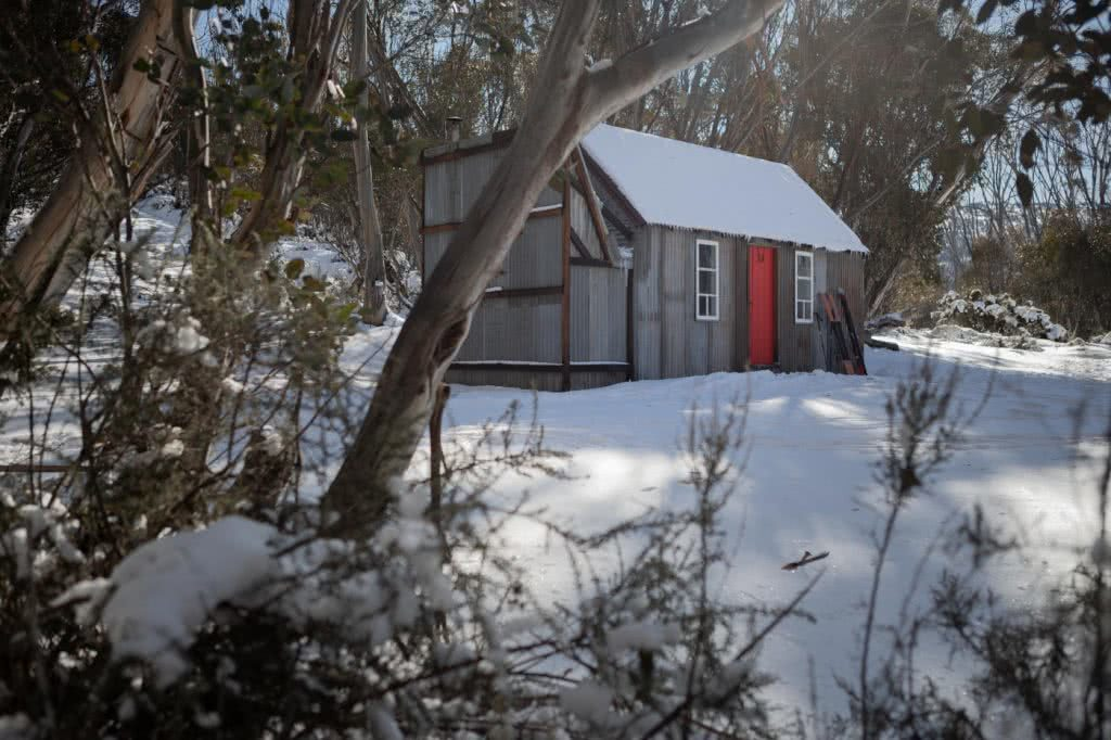 Snowshoeing Across The Aussie Alps, hut, red door, snow, gumtrees