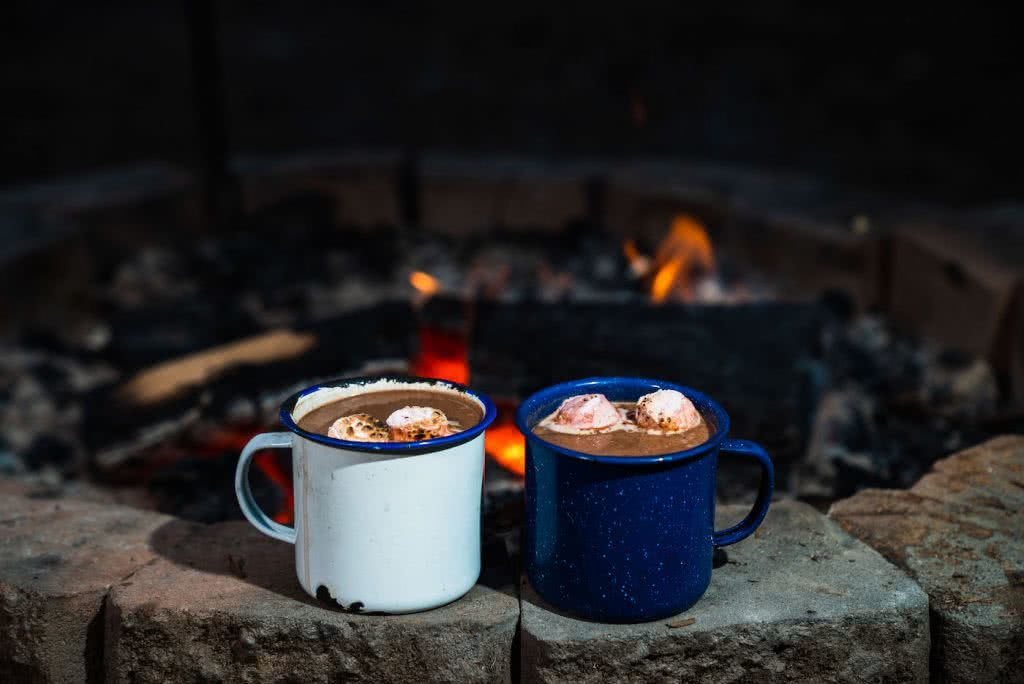 This Boozy Hot Choccy Is The Perfect Nightcap For Camping, photo Jonathan Tan, campfire, cups, hot chocolate, marshmallows