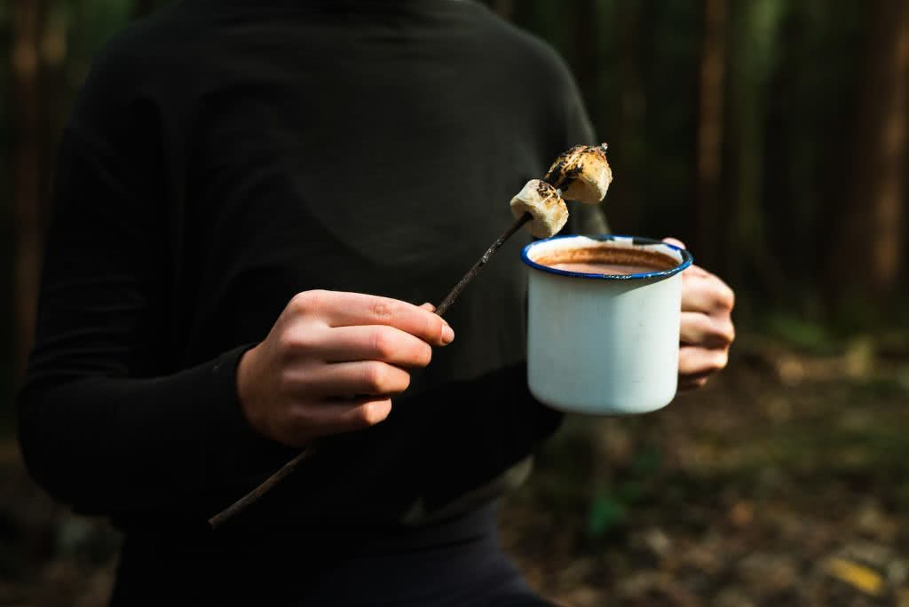 This Boozy Hot Choccy Is The Perfect Nightcap For Camping, photo Jonathan Tan, marshmallows, stick, cup, woman