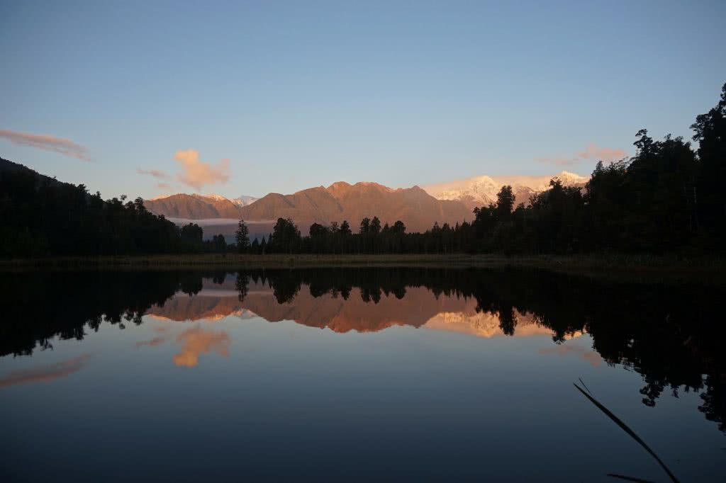 Make New Zealand Your Next Solo Road Trip Destination, Amy Fairall, reflection, Mt Cook, sunset, Lake Matheson, mountains, snow capped, trees