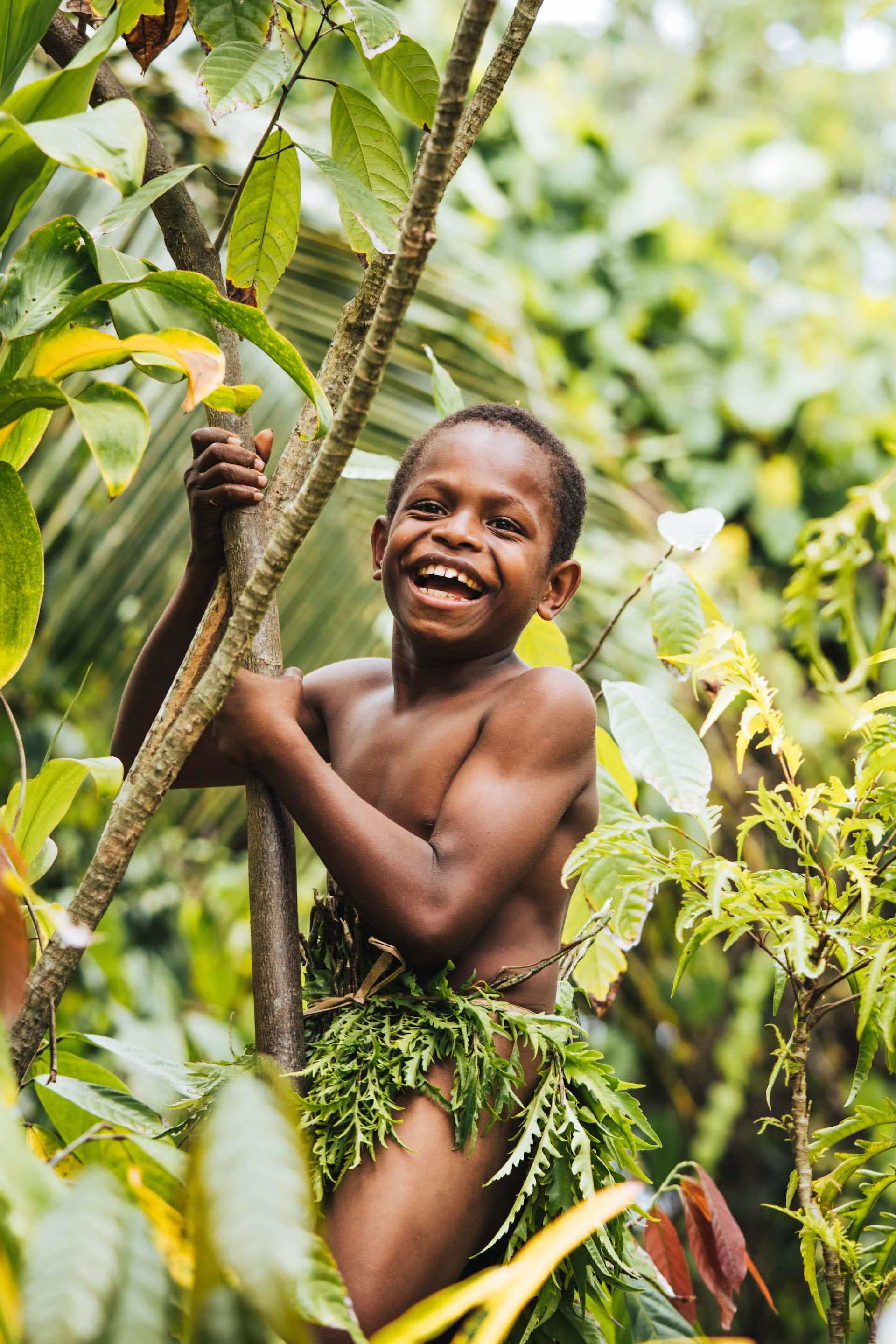 An Insider's Guide To Malekula Vanuatu , Ruby Claire, photos by Ain Raadik and Ben Savage, boy, tree, climb, laughing, Big Nambas