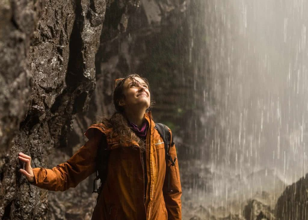 photo by Miranda Fittock, woman, waterfall, hike, rain, jacket