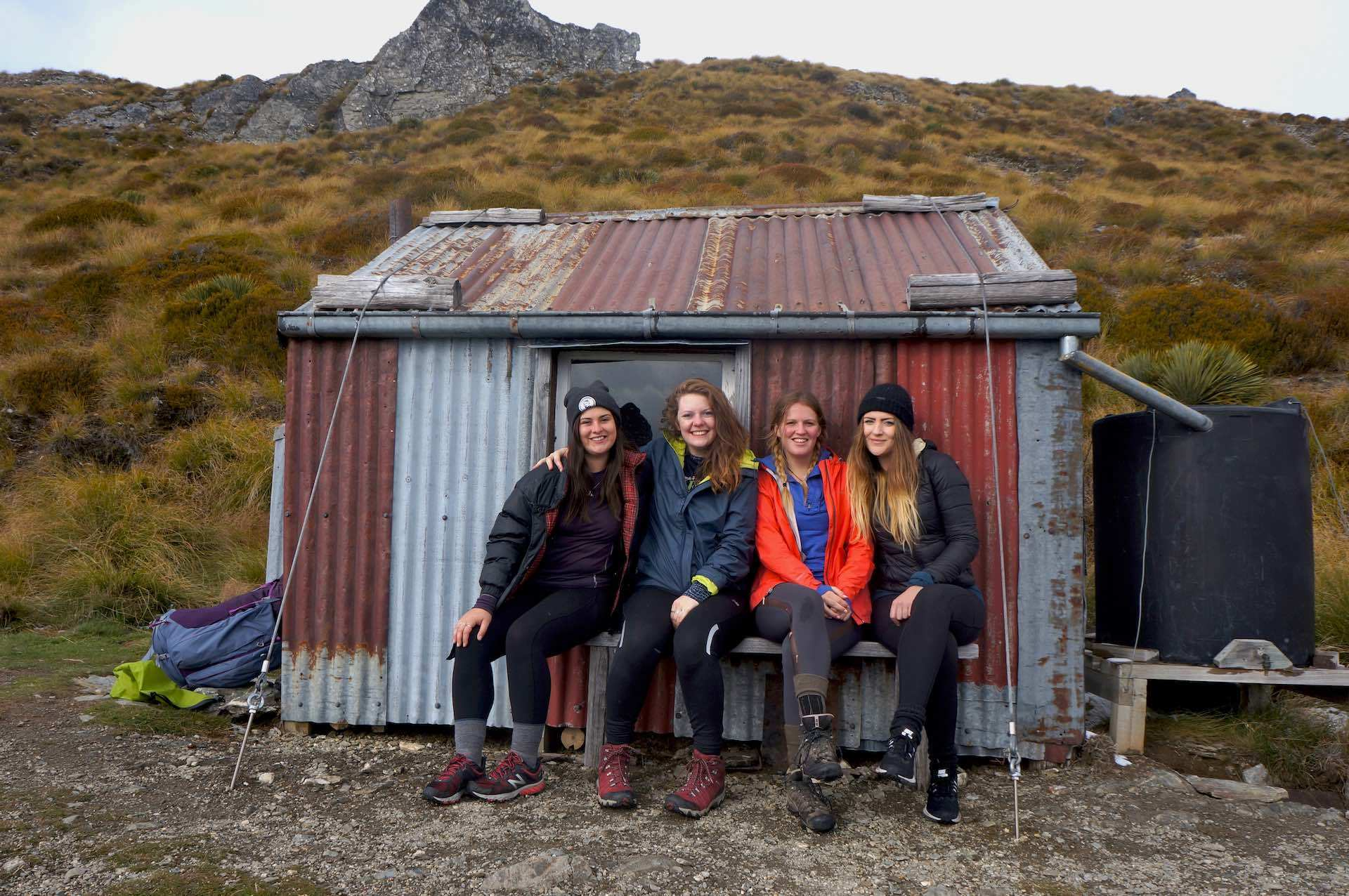 Hike to Heather Jock Hut For Jaw Dropping Mountain Views, Arden Haar, NZ, hut, friends, women, sit, mountain