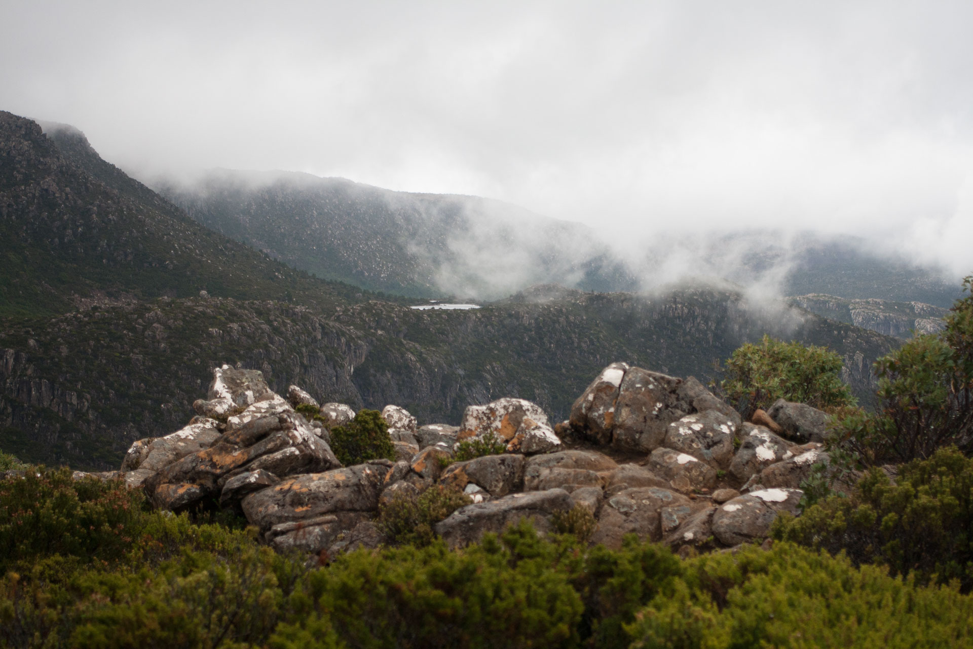 The clouds clear to reveal the first Tarn in the distance, The Tarn Shelf – Tasmania's Best Day Hike You've Never Heard Of, casey fung, tarn shelf, mt field national park, tasmania